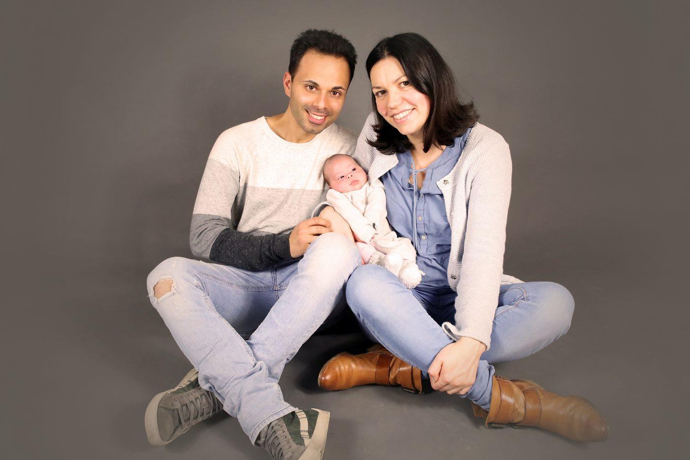 Familienfoto mit Baby mit grauem Hintergrund