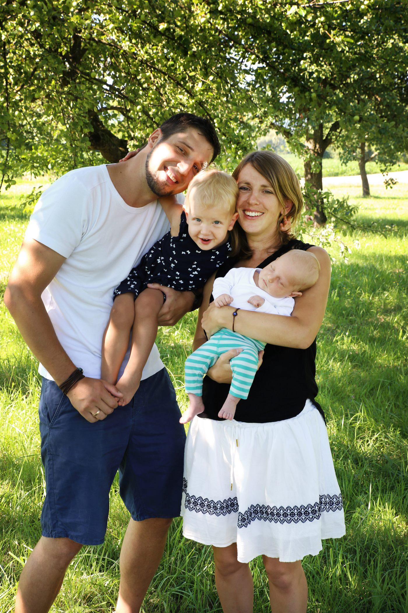 Glückliche Familie beim Familienshooting unter Obstbäumen