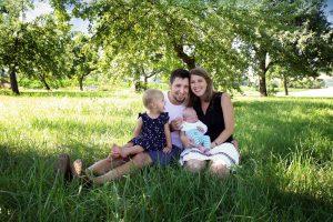 Familie im Gras sitzend beim Familienshooting in Farbe