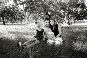 Familie im Gras sitzend beim Familienshooting in schwarz-weiß