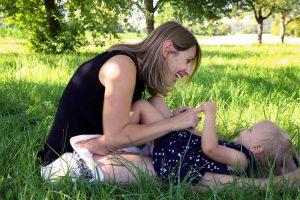 Mutter mit Kind liegend im Gras beim Familienshooting