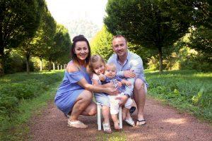 Glückliche Familie kniened vor Baumallee fotografiert