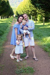 Glückliche Familie vor Baumallee fotografiert