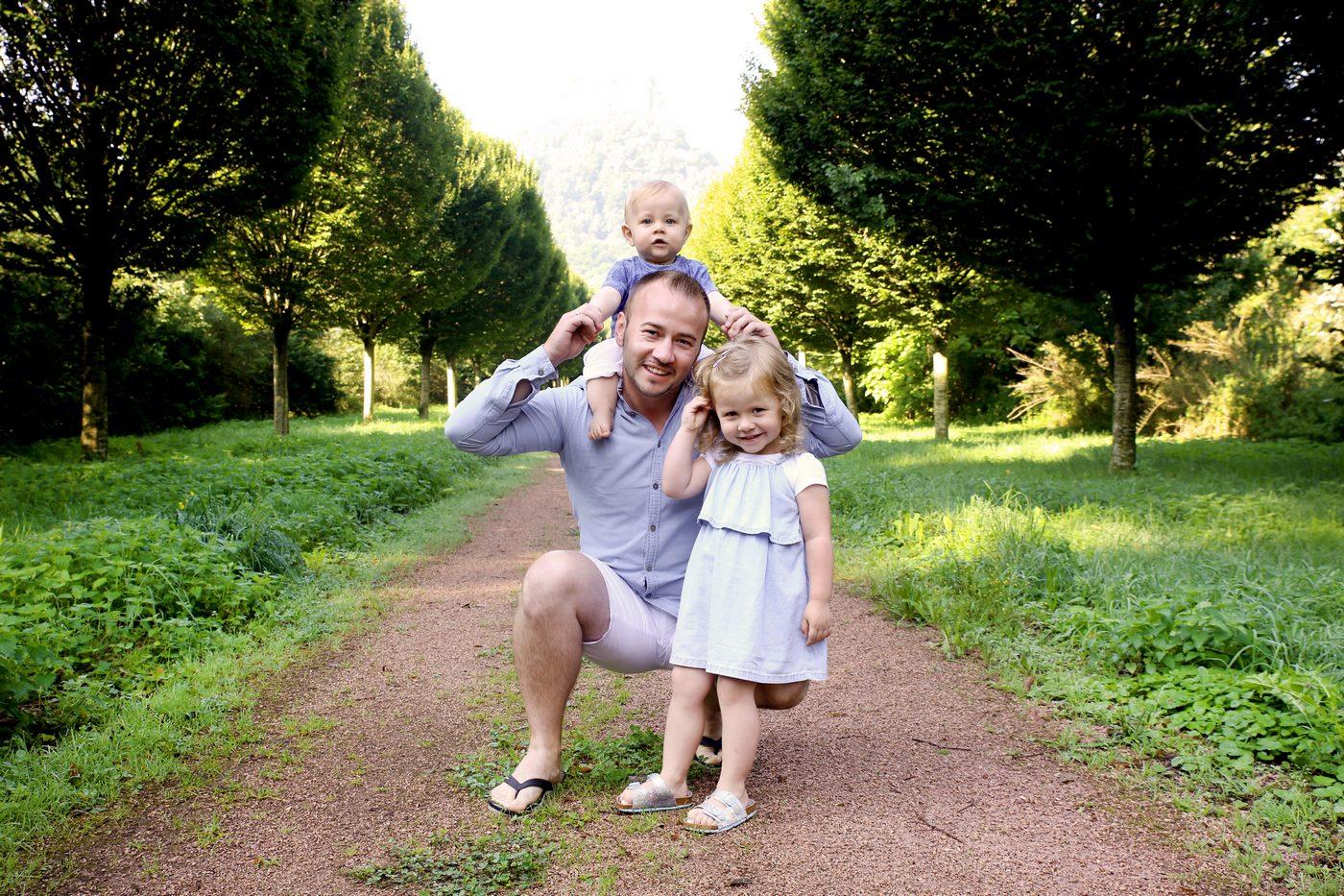 Vater mit Kind knieend mit Kind auf der Schulter abgelichtet