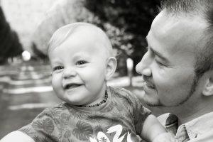 Vater mit Kind vor Baumallee fotografiert