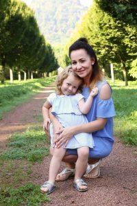 Mutter mit Kind knieend vor Baumallee