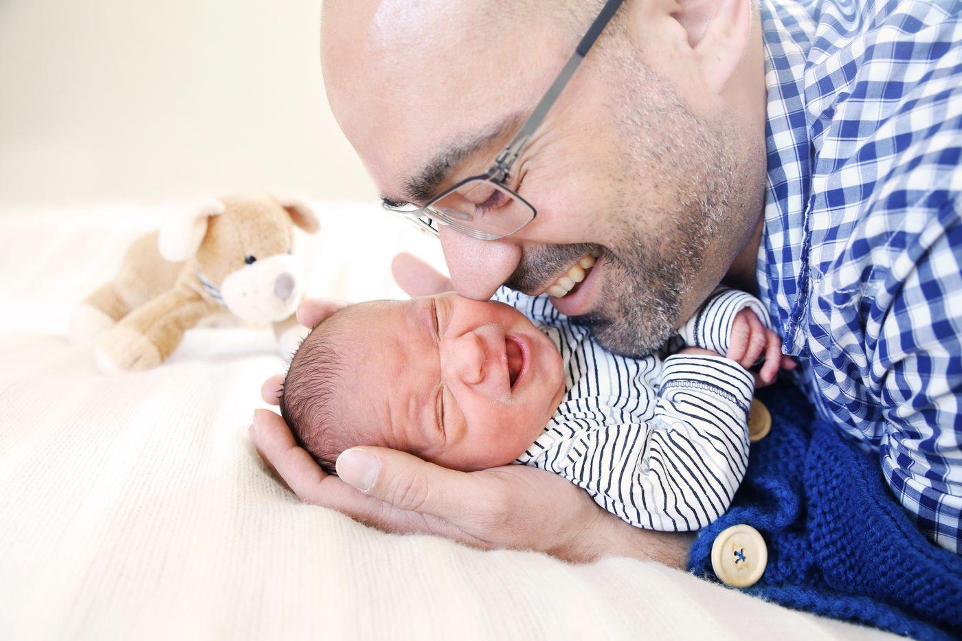 Vater lacht sein neugeborenes Baby an