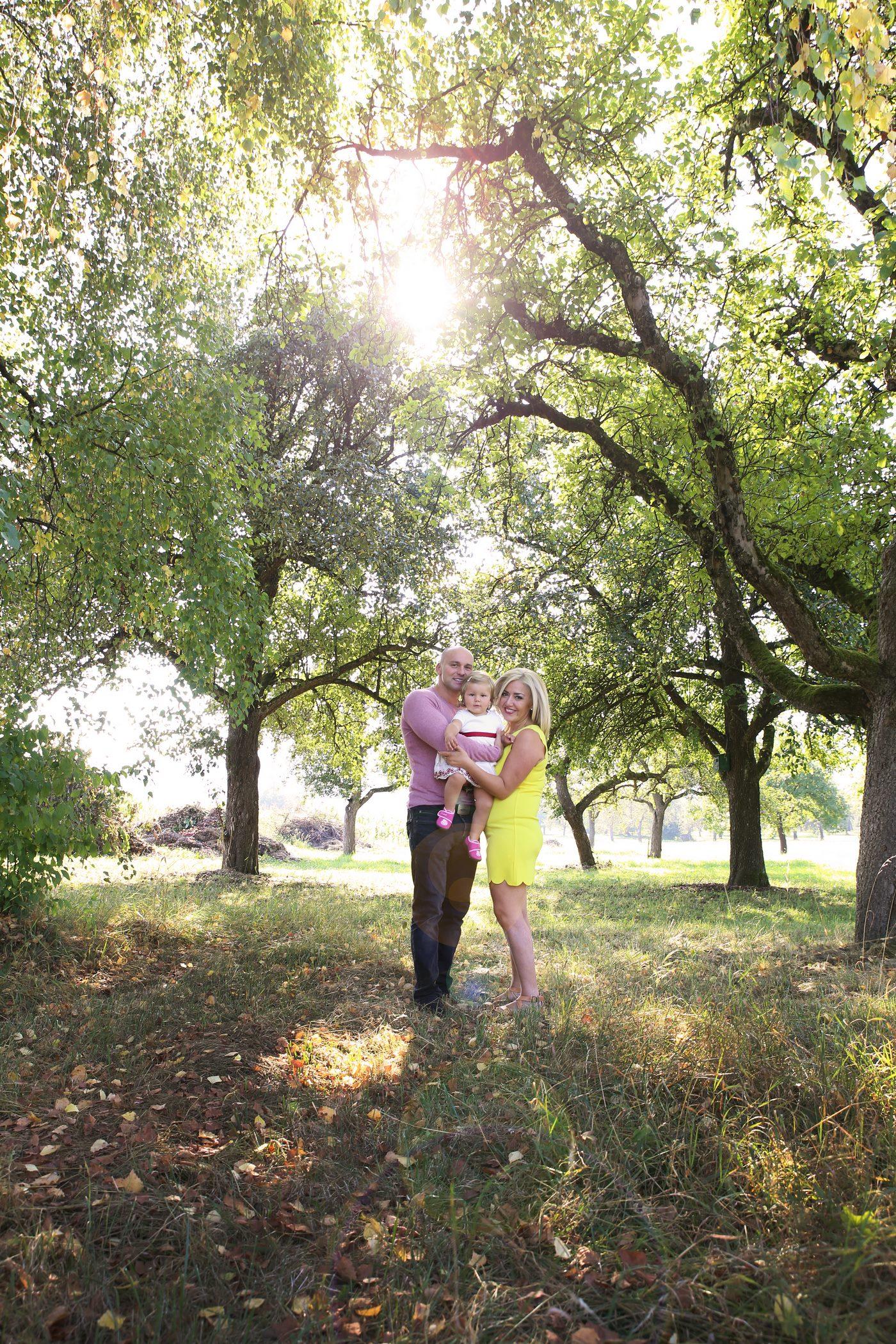 Foto einer Familie unter Obsbäumen während die Sonne durch die Baumkrone scheint