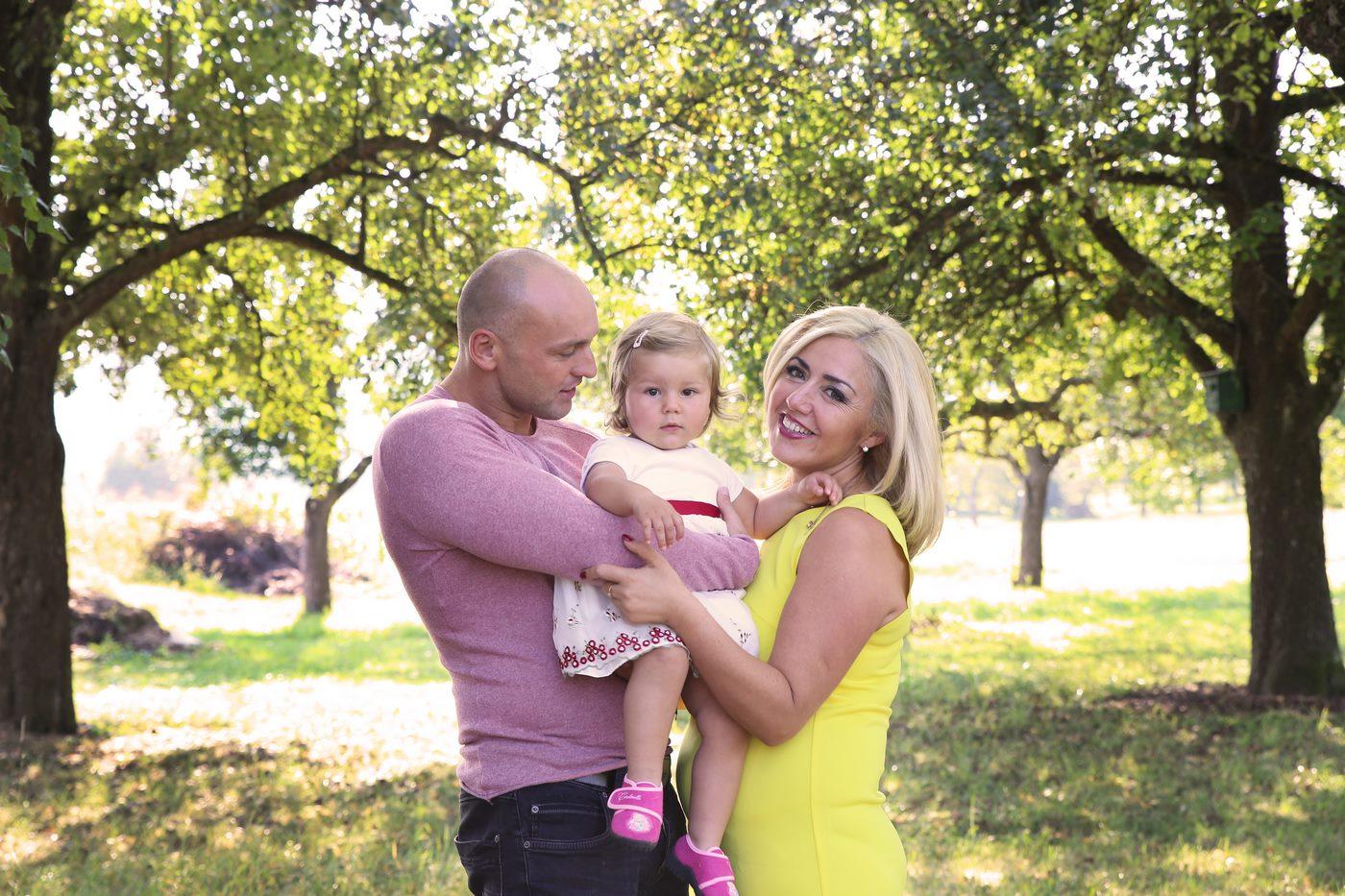 Familienshooting unter Obstbäumen während Mutter in die Kamera schaut