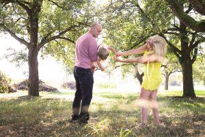 Kind möchte zur Mutter während es beim Vater auf dem Arm liegt fotografiert unter Obstbäumen