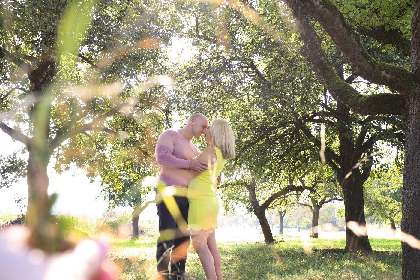 sich küssendes Ehepaar unter Obstbäumen