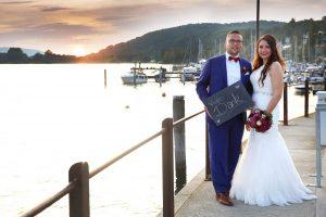 Bräutigam mit blauem Anzug hält eine Schild mit dem Schtiftzug vielen Dank in der Hand