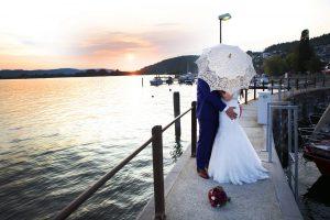 Brautpaar am Bodensee fotografiert verteckt sich unter einem Schirm im Vintagelook