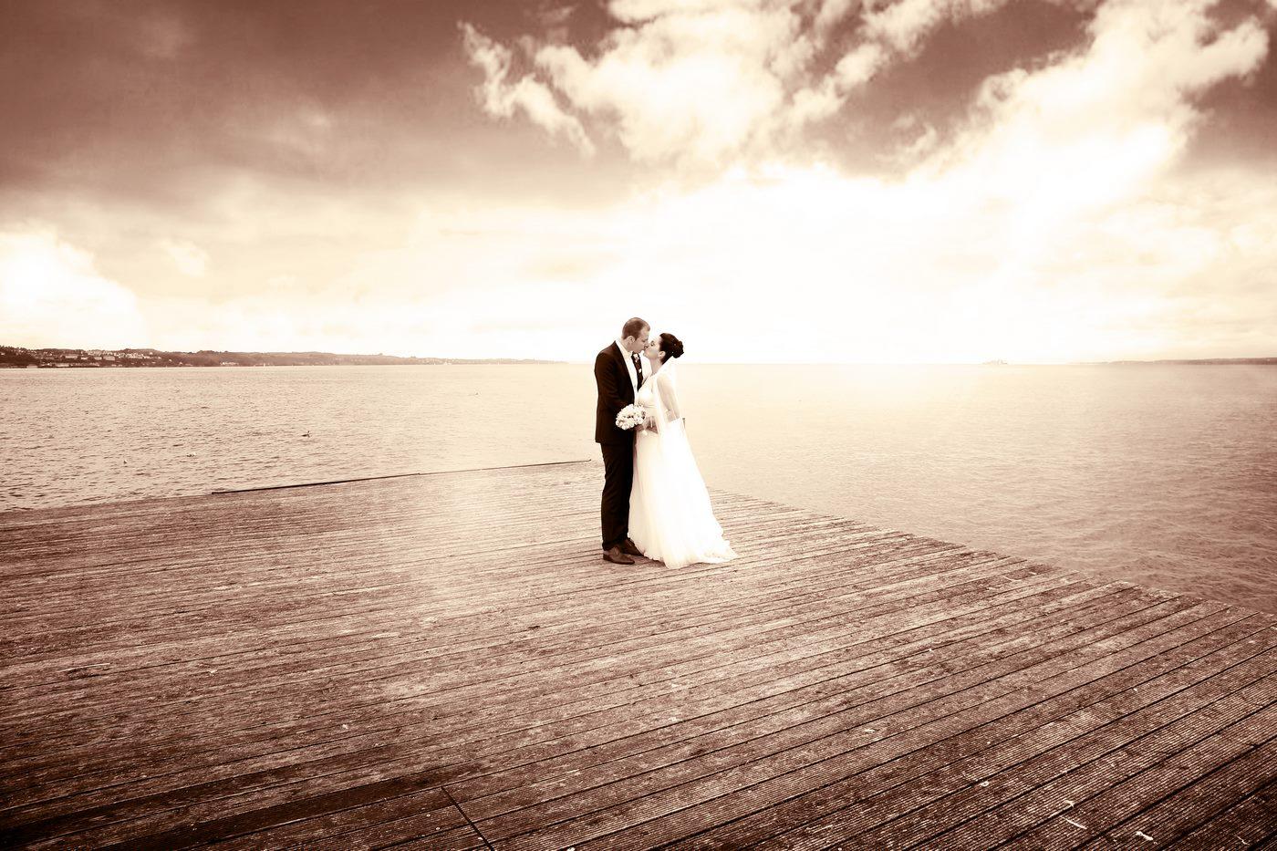 Brautpaar steht auf Floss inmitten des Bodensees in Sepia