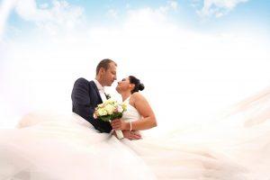 Brautpaar schaut sich unter blauem Himmel in die Augen
