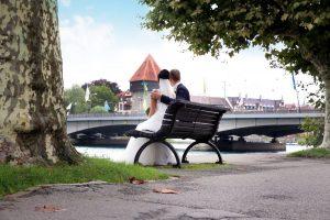 Brautpaar sitzend am Rheinufer mit Blick auf Konstanz