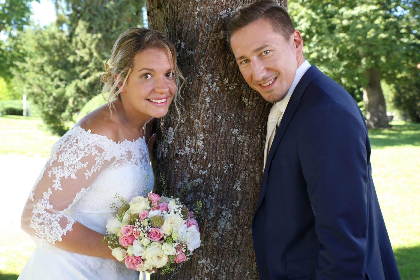 Brautpaar an Baum lehnend und in die Kamera schauend