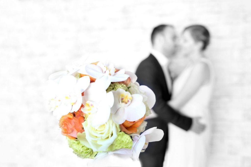 Blumen fotografiert mit Brautpaar verschwommen im Hintergrund