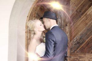 Brautpaar küsst sich an einem Holztor