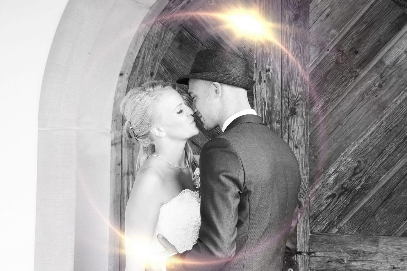 Brautpaar küsst sich an einem Holztor schwarz-weiß