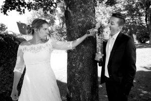 Braut schaut böse auf Bräutigam und lässt ihn Blumen essen