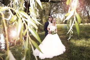 Brautpaar während Hochzeitsfotografie unter einem Baum