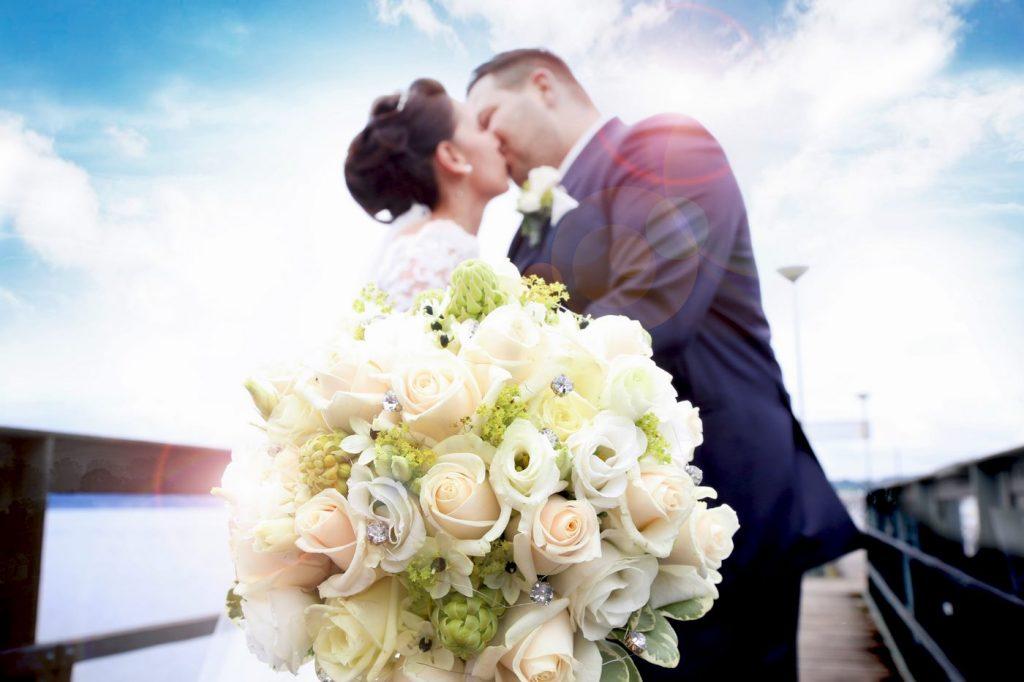 Brautpaar küsst sich auf einem Bootssteg und hält einen Brautstraußin die Kamera