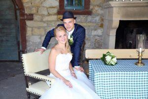 Ehemann mit Hut stehend hinter seiner Frau während eines Hochzeitsshootings