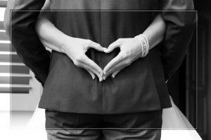Braut umarmt Ehemann und formt ein Herz mit ihren Händen