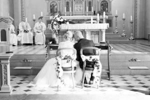 Brautpaar vor dem Altar in der Kirche sitzend