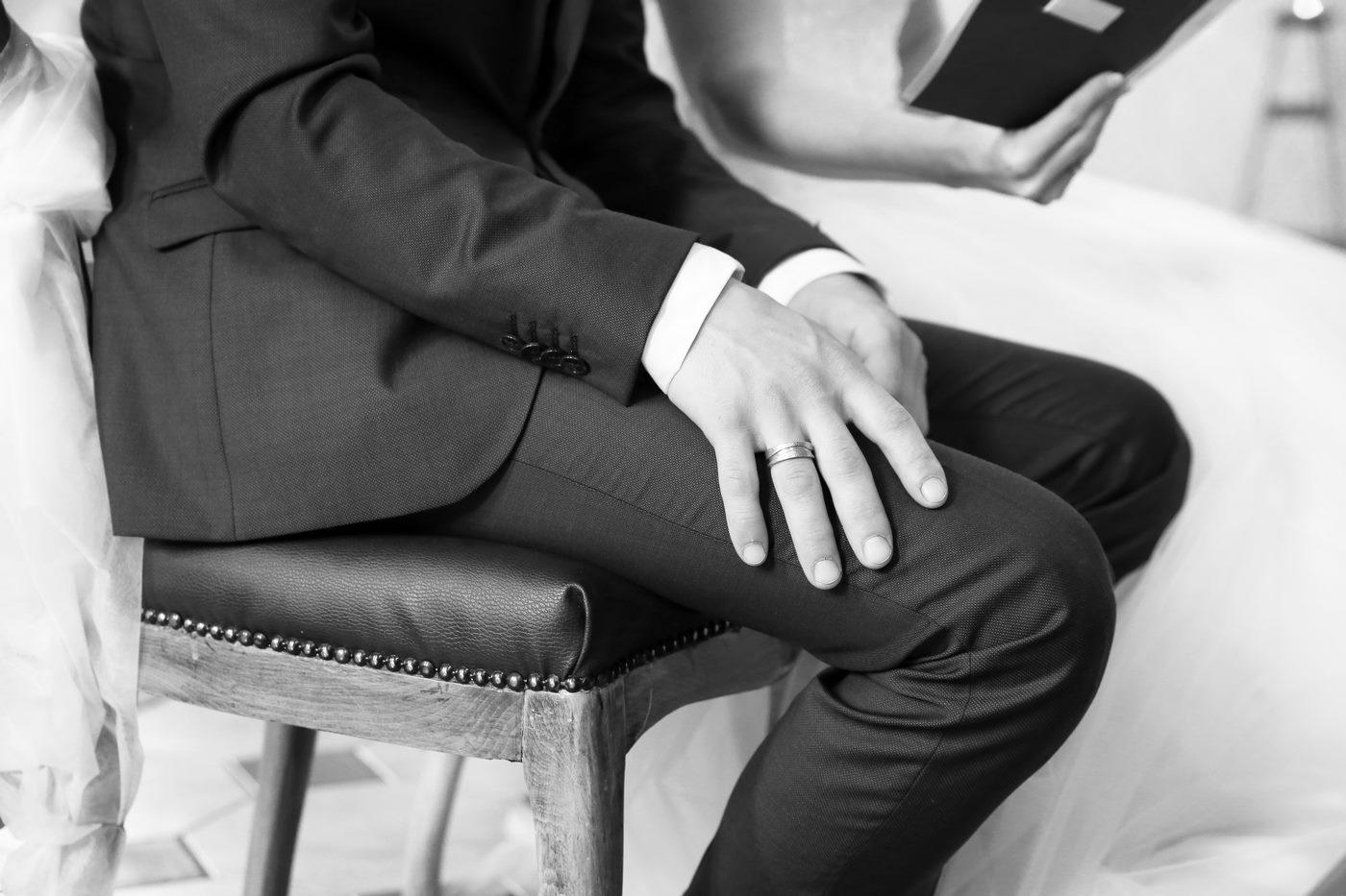 Ehemann hält während Traun seine Hand auf dem Schoß in schwarzweiß fotografiert