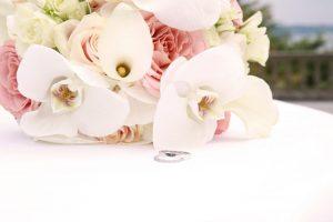 Eheringe vor einem Blumenstrauß fotografiert