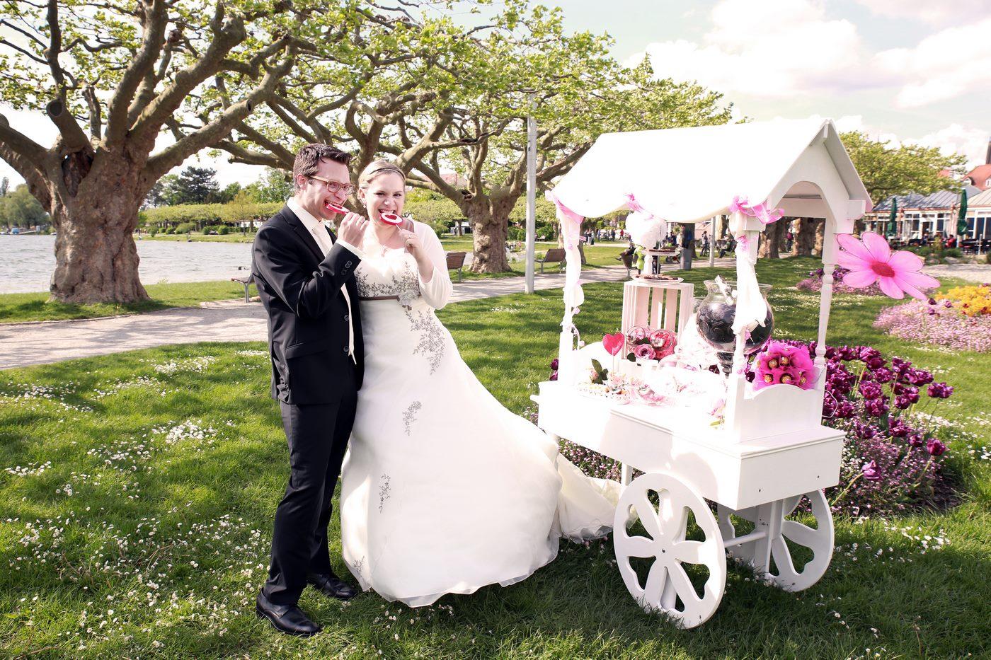 Brautpaar beißt in Lutsche neben einem Candycart