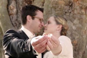 Brautpaar Nase an Nase und präsentieren ihre Eheringe