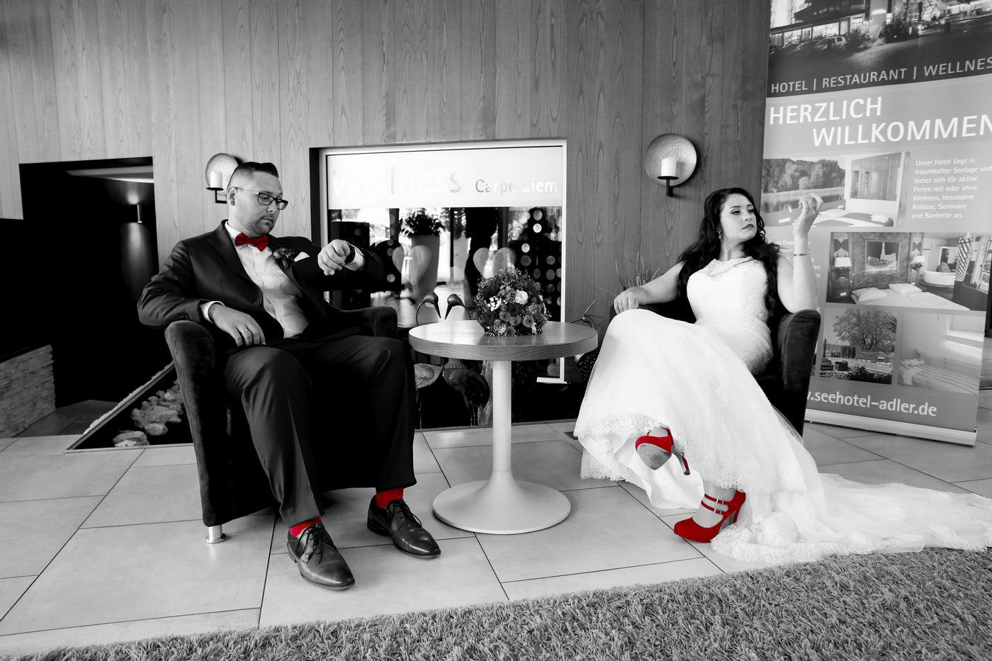 Brautpaar wartet in Hotellobby des Seehotels Adler mit roten Akzenten