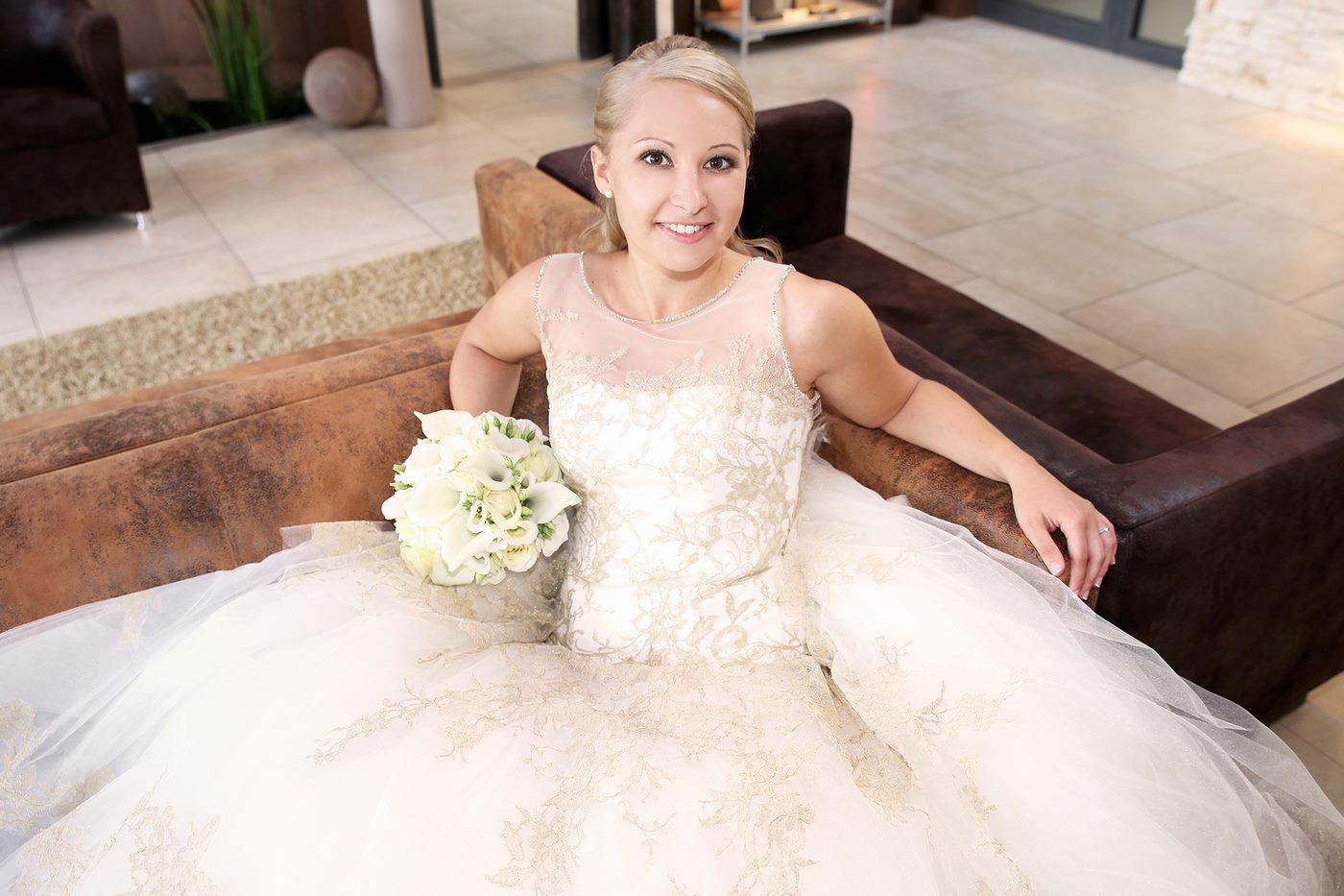Braut ganz in weiß sitzend im Sofa