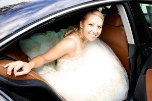 Braut mit weißem Brautkleid im Auto fotografiert
