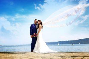 Brautpaar am Bodensee fotografiert und der Schleier weht im Wind