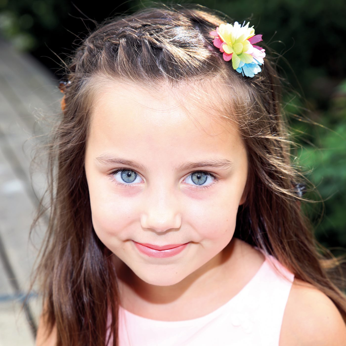 Mädchen mit strahlenden Augen und Blume im Haar fotografiert im Kindergarten