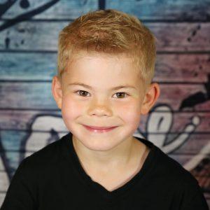 Junge lacht im Kindergarten und wird fotografiert