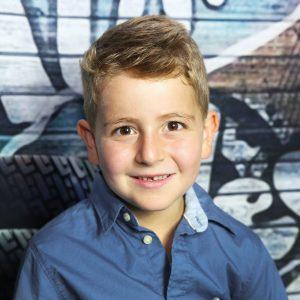 Junge mit Zahnlücke fotografiert im Kindergarten