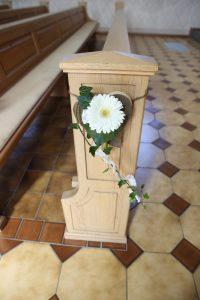 Blumenschmuck in der Kirche an heller Bank