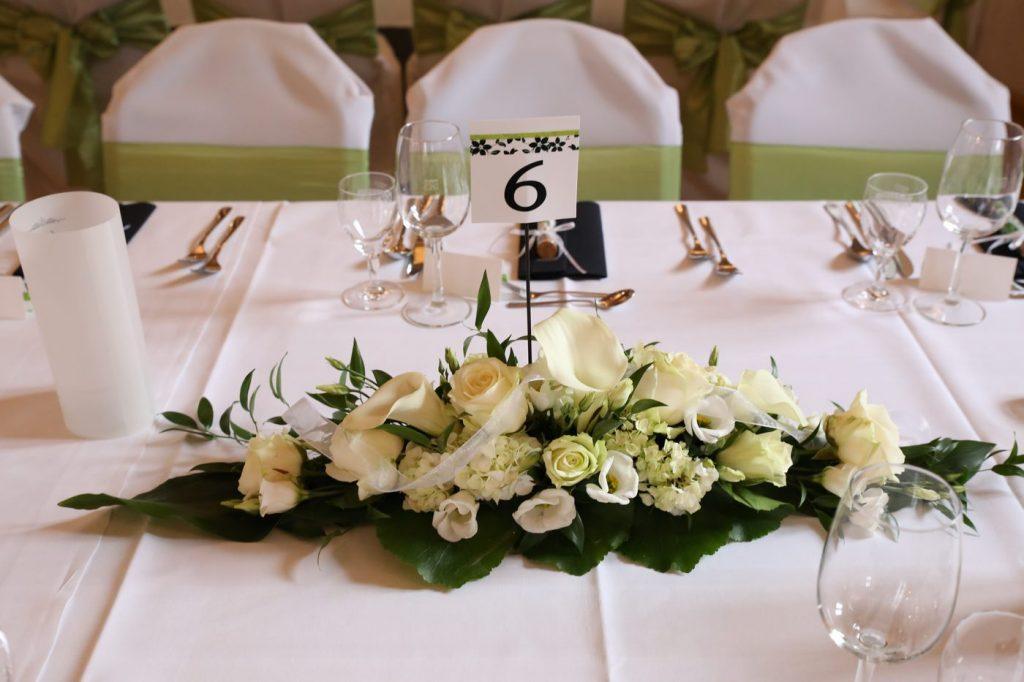 Blumengesteck auf Hochzeitstisch mit Tischnummer 8 in der Mitte und grünen Stuhlschleifen