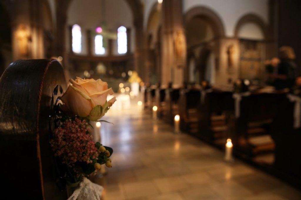 Kirche von innen mit Kerzen beleuchtet und mit Blumen geschmückt