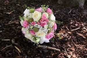 Brautstrauß in weiß-rosa und Eheringe auf Waldboden