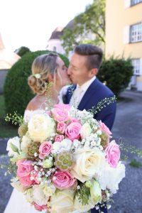 Brautstrauß im Vintage Stil mit küssendes Brautpaar im hintergrund