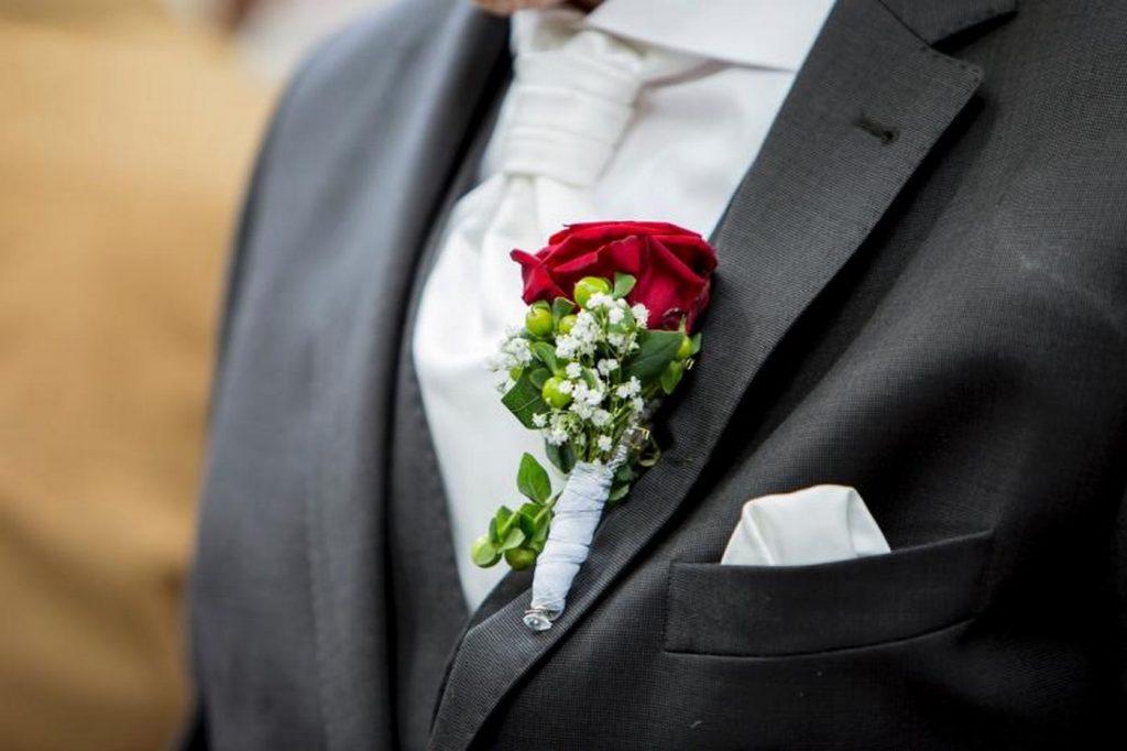 Rote Rosa als Anstecker an einem schwarzen Sacko
