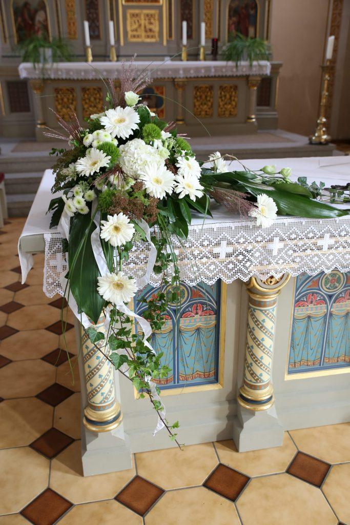 Großes Blumengesteck an einer Ecke des Kirchenaltars