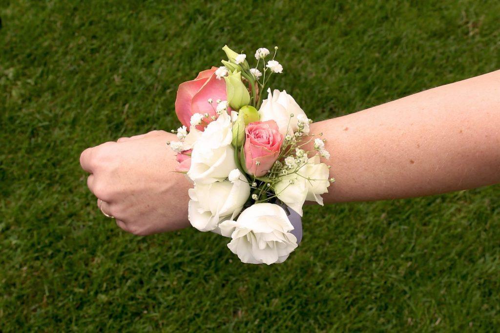 Blumenarmband an Handgelenk in weiß rosa gehalten
