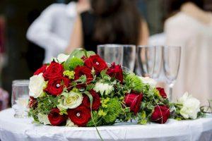 Rotes Blumengesteck mit Sektgläser im Hintergrund